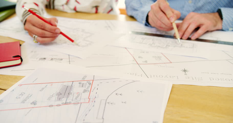 Steadicam of male and female architects working on blueprints in their office. Female draftsperson and male design engineer collectively working on construction design blueprints. Shot on RED Camera | Shutterstock HD Video #1023598660