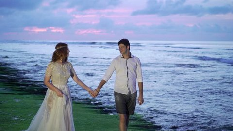 Newlyweds walking on the beach near sea at the evening or sunset. Holding hands, hugging. Romantic near ocean. Tropical vacation.