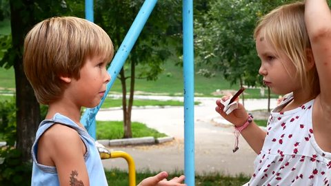 Friends eat chocolate in the park. The girl shares with the boy