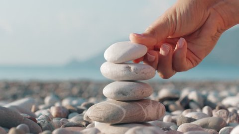 Hand making stone tower on sea beach. Close up of stack of balanced pebbles on beach. Woman making pyramid of stones for meditation at summer holidays