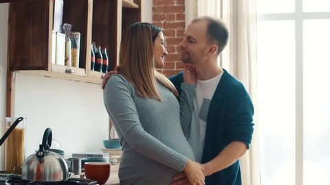 Pregnant woman and her husband in kitchen at home