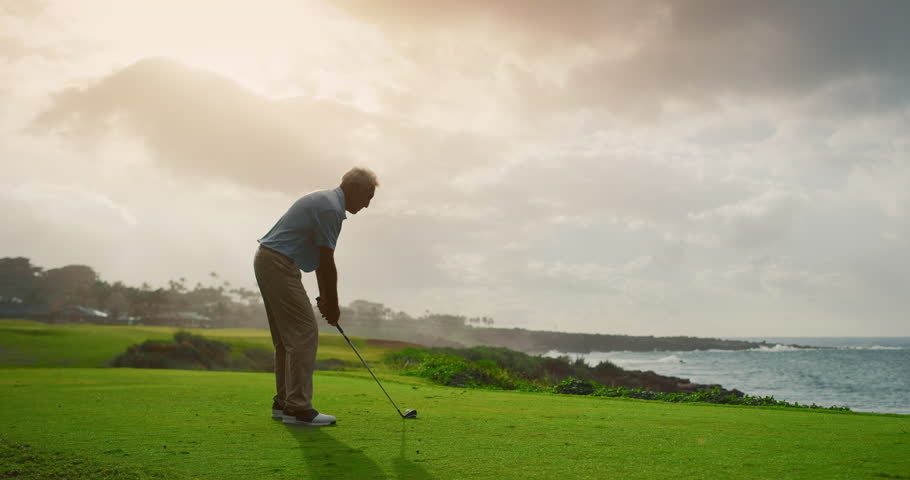 Handsome older golfer swinging and hitting golf ball on beautiful course at sunset by the ocean, slow motion