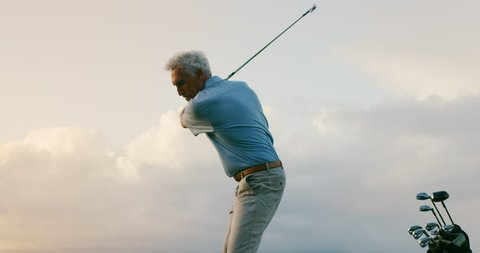Tight shot of handsome older golfer swinging golf club with clouds, golfing in paradise, slow motion