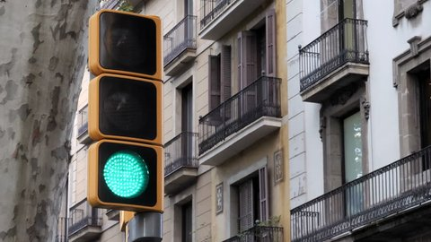 Red, yellow and green modern traffic light in town. Urban cityscape in background. Blinking and changing color traffic light in front of vintage style beautiful architecture. Spain, Barcelona