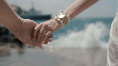 Beautiful Couple Walking On The Beach. Lovers Hold Hands. Santorini Island, Greece. Close-up.