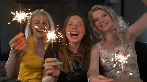 Three sexy ladies happy dancing with sparklers and flirting with You. Super slow motion shot. Focused on sparkling light.