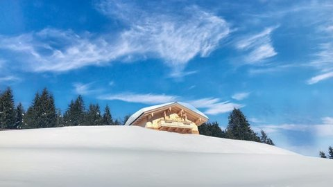 Snow covered chalet or alpine cottage in the mountains agsinst great blue sky