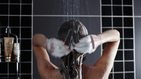 Woman washes her hair with shampoo in the shower with, hair care, ceratin mask, rinse shampoo and balm, strong hair, washing hair