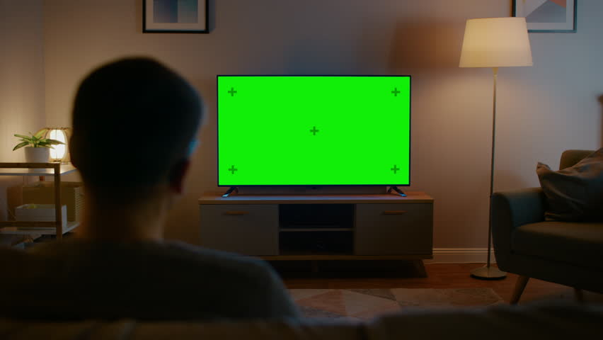 Young Man in Glasses is Sitting on a Sofa and Watching TV with Horizontal Green Screen Mock Up. It's Evening and Room at Home Has Working Lamps. | Shutterstock HD Video #1023697390