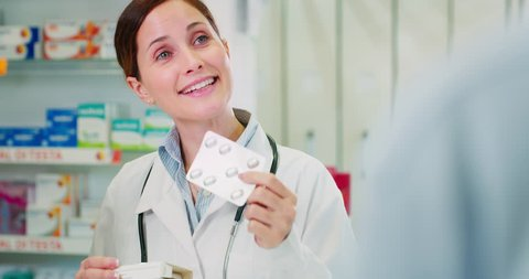 Slow motion of young woman pharmacist handing over prescribed medicines to a patient in drugs store. Shot in 8K. Concept of profession, medicine and healthcare, medical education,pharmaceutical sector