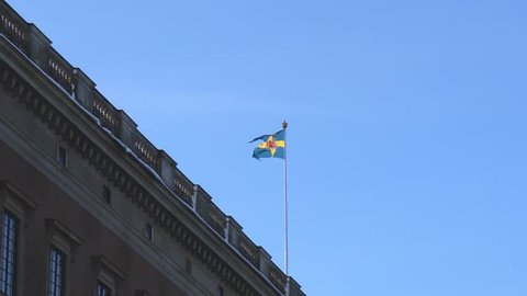 Stockholm / Sweden - February 2 2019: Swedish flag swings on the roof of the government building during Winter.