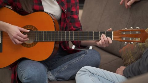 Young beautiful girl plays an acoustic guitar and kiss her boyfriend after that