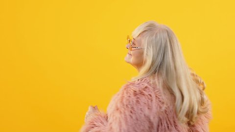 Stylish granny in pink fur and eyeglasses moving to music, dancing party, style