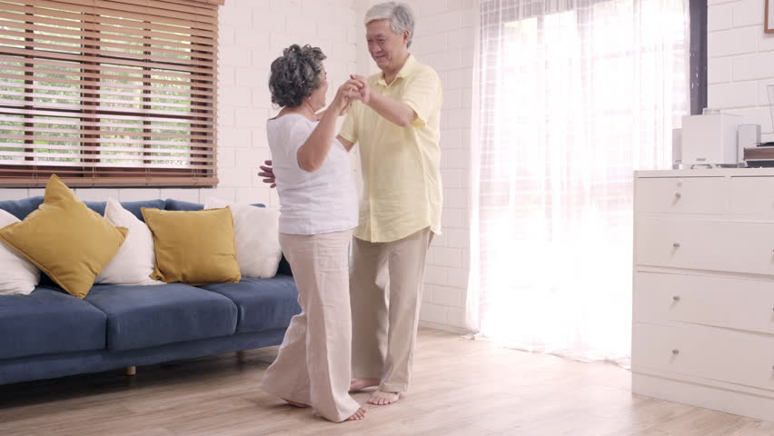 Asian elderly couple dancing together while listen to music in living room at home, sweet couple enjoy love moment while having fun when relaxed at home. Lifestyle senior family relax at home concept. | Shutterstock HD Video #1023749500