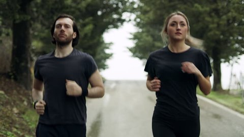 Fit man and woman running along a quiet street in Tuscany, with soft overcast lighting. Wide shot on 8k helium RED camera.