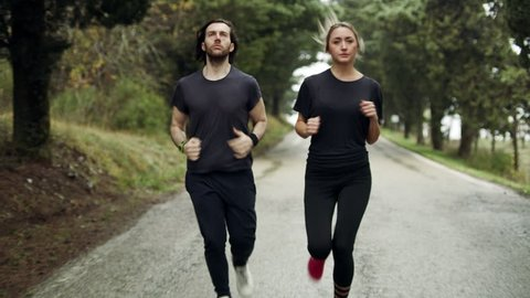 Live a healthy, fit lifestyle with this shot. A fit couple running along a quiet street in Tuscany. Close to wide helium RED, 4k. Get it now.