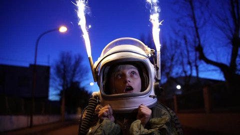 Little Girl with the astronaut helmet in the street with bengal light