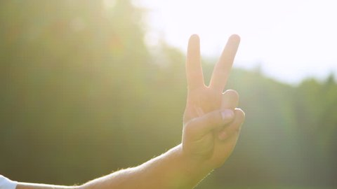 SLOW MOTION, CLOSE UP, LENS FLARE, DOF: Bright golden sunbeams shine on male hand and showing the peace sign. Unrecognizable young man shows the victory sign to the camera on a sunny summer day.