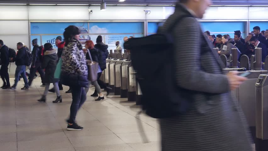 London Canary Wharf, UK - Feb 7, 2019: Office worker commuters at rush hour pass ticket machines barriers at London's Canary Wharf underground station