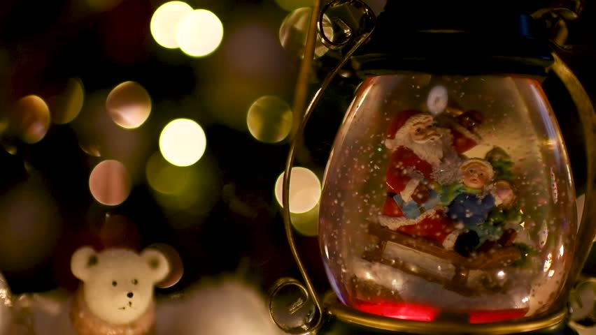 Beautiful color change snow globe with Santa Claus and child on sleigh with Christmas lights blurred in the background. Flat plane