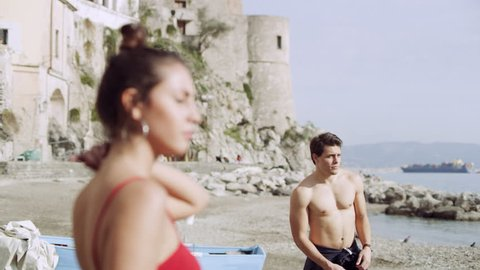 Beautiful Italian woman checking out a handsome guy as he walks by on the beach of the Amalfi Coast. Medium shot on 8k helium RED camera.