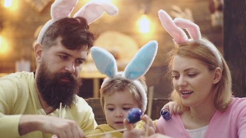 Close-up of happy family which are painting easter eggs. Cute little child boy wearing bunny ears. mother, father and their son painting Easter eggs. Easter eggs on wooden background