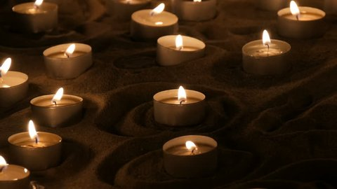 A large number of small white round candles burning in the sand. Background of burning wax candles