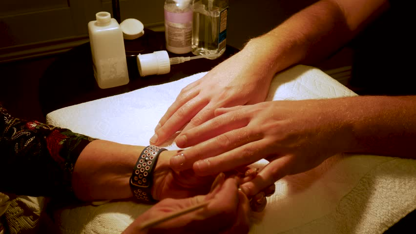 Close up of a man's large hands getting a manicure #1024005920