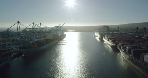 Aerial footage waterway between shipping cargo containers in the harbor and port docked in Long Beach outside Los Angeles, California United States