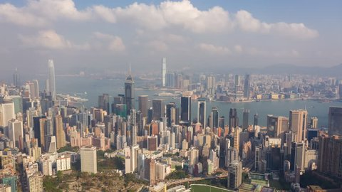 HONG KONG - MAY 2018: Aerial timelapse view of Causeway Bay, Wan Chai and Victoria Bay, residential and office buildings and skyscrapers. Sunny day with clouds