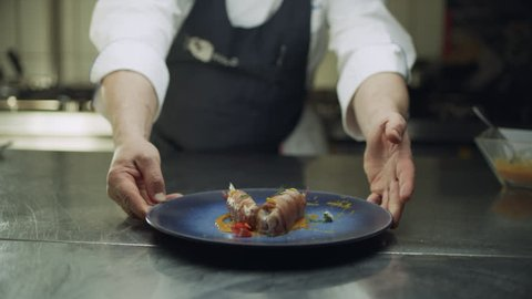 Professional chef plating a delicious dish of large shrimp wrapped in prosciutto on a blue plate. Medium shot on 8k helium RED camera.