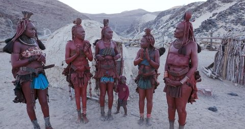 4K view of Himba woman in traditional dress dancing and singing outside their clay hut, Namibia