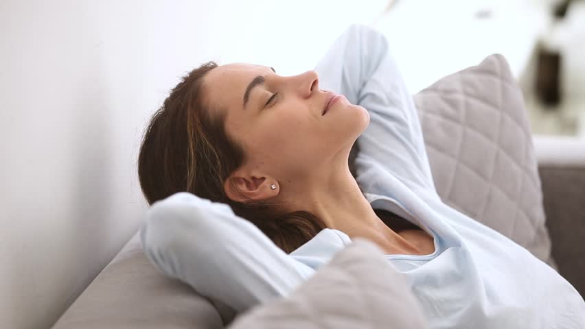 Calm relaxed young woman resting leaning on comfortable soft sofa chilling taking healthy nap at home, serene girl breathing fresh air dreaming enjoy peaceful mood lounge feeling no stress concept    Shutterstock HD Video #1024093430
