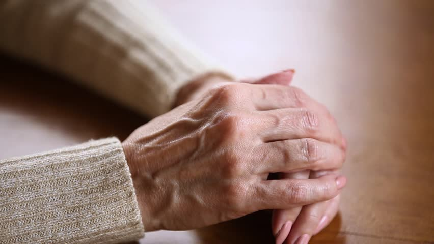 Old lonely mature female wrinkled skin hands folded on table close up view, middle aged senior elderly woman grandmother having arthritis rheumatism, health care, aging process and loneliness concept