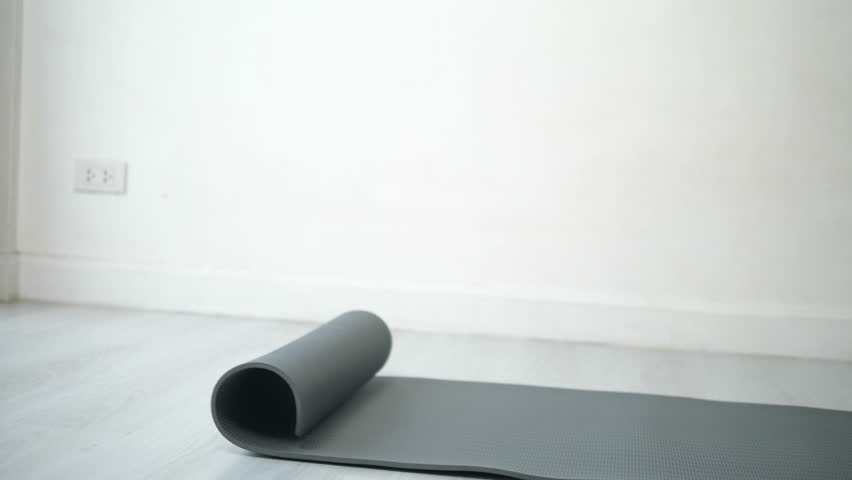 Fitness equipment, sport and healthy lifestyle concept - woman rolling up mat at yoga studio or gym | Shutterstock HD Video #1024098590