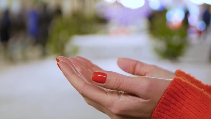 Female hands holding a conceptual hologram with woman body. Woman with red nails and sweater with future holographic technology on a blurred background of the street | Shutterstock HD Video #1024152860