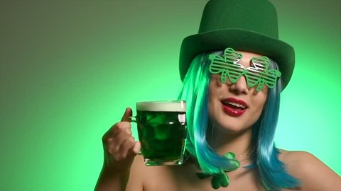 St. Patrick's Day leprechaun model girl in green hat holding mug of Green Beer pint and over green background, Dancing, Smiling. Patrick Day pub party, celebrating. Green beer. Ads. 4K UHD slow motion