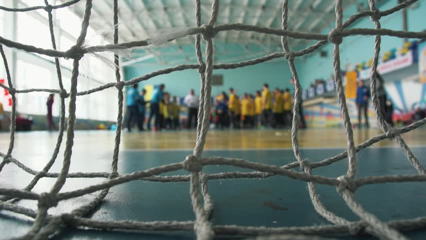 Pupils hit the ball into the goal.Net on foreground, ball hits the camera.School competitions in sports hall | Shutterstock HD Video #1024166240