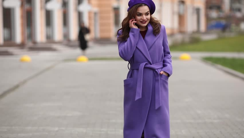 Stylish woman in purple coat and beret talking on phone in the street. | Shutterstock HD Video #1024167080