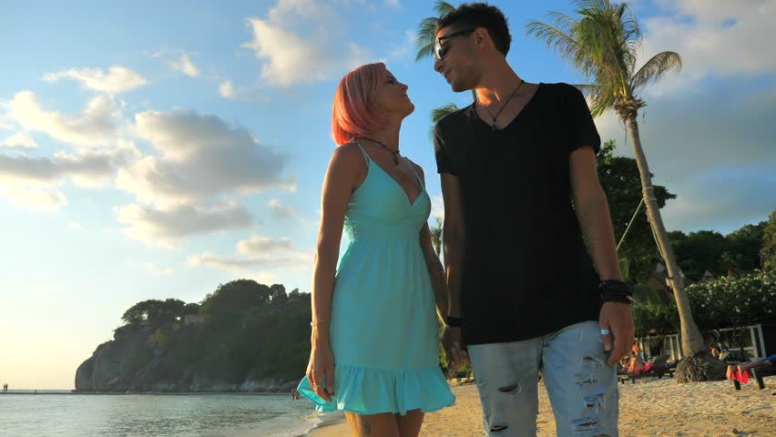 Happy romantic young couple enjoying Beautiful Sunset Walk on the Beach