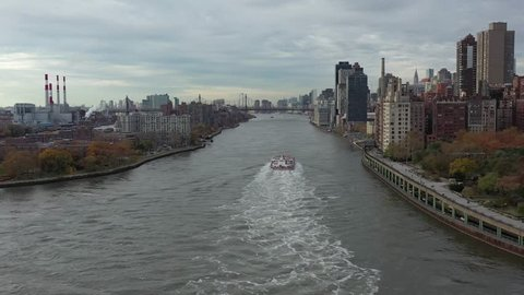 Drone chase of tanker ship between Roosevelt and Manhattan islands in NYC as it heads toward the Queensboro Bridge. Views of Manhattan and Queens skylines and traffic on the FDR drive. in 4K.