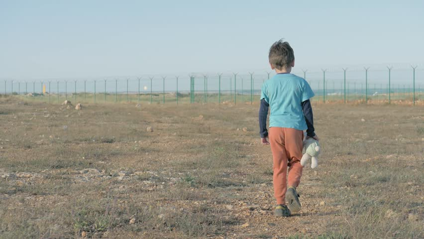 view from the back of juvenile child leaving moving towards Mexican border. Unhappy Abandoned Lonely boy walk with her Friend Teddy bunny Toy desert terrain on the state border. concept Poor Children