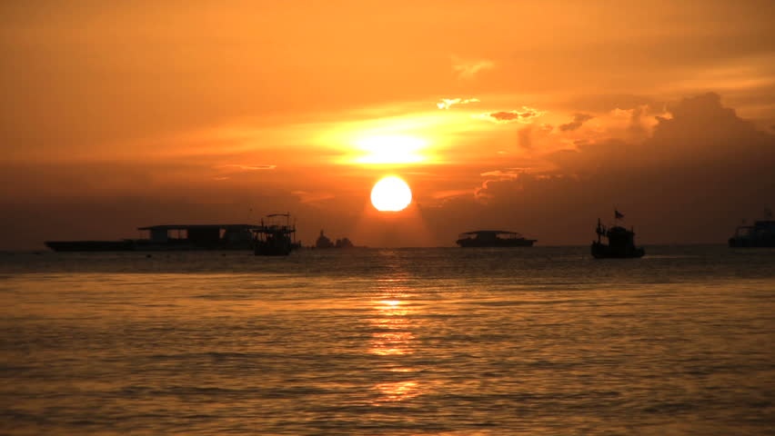 boats anchored in Pattaya Bay, Thailand while the sun sets.