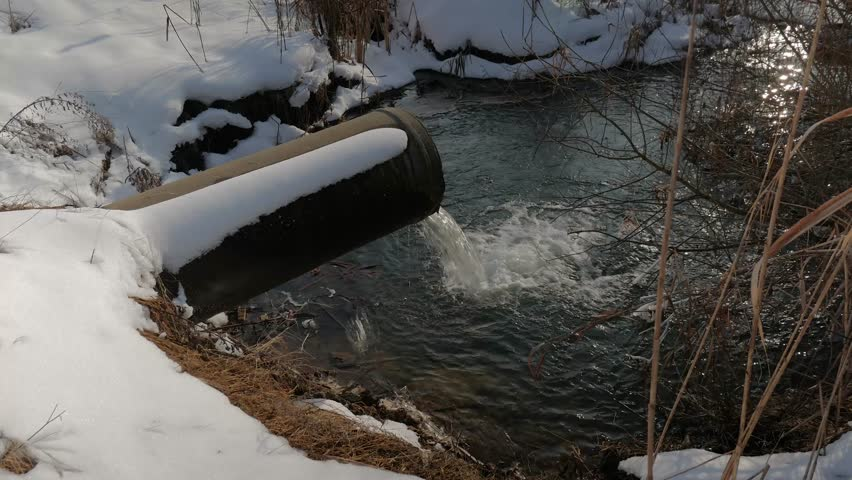 Concrete pipe transporting the polluted water in to a small pond at wintertime, on late evening, sunset. | Shutterstock HD Video #1024271060