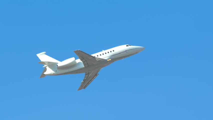 Generic Unmarked Executive Jet Close-up Flying Up into a Clear Blue Sky on a Sunny Day