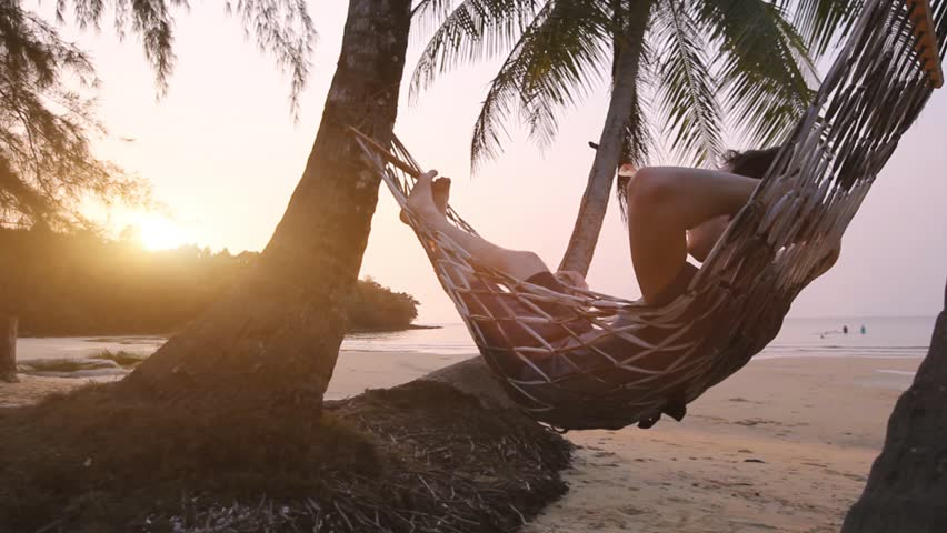 Tropical getaway, tourist relaxing in beach hammock, exotic retreat | Shutterstock HD Video #1024326530