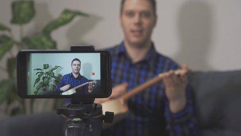 Handsome man making video blog about musical instruments.