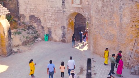 Diu, Gujarat, India - Circa 2018: Families and people entering the famous landmark fort diu through the main gate in gujarat. Shows the amazing stone arch gate and buildings around this famous tourist