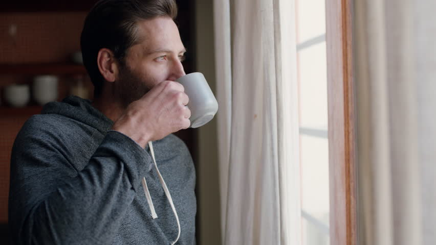 Young man opening curtains looking out window enjoying fresh new day feeling rested drinking coffee at home | Shutterstock HD Video #1024419800