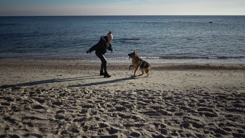 ODESSA, UKRAINE - 02 FEBRUARY, 2019:  girl plays in the winter in Odessa on the beach near the water with a big dog, a German shepherd